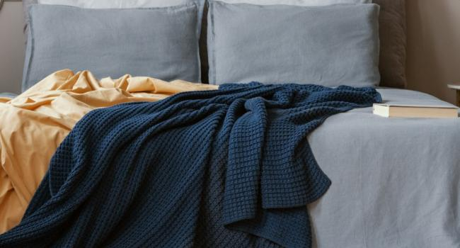 dark-blue-and-orange-blankets-on-comfortable-double-bed-in-grey-picture-id1203040741